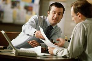Two businessmen discussing paperwork at desk
