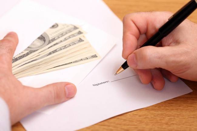 Businessman signing a contract and getting money for it